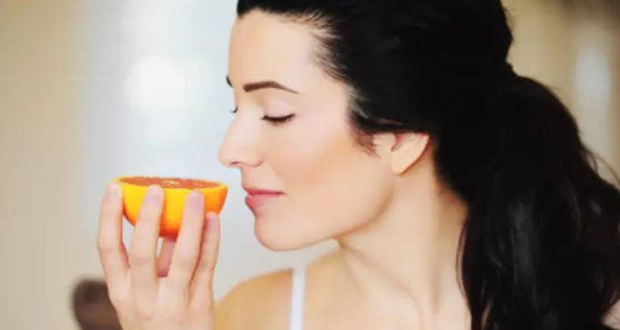 Woman Smelling Orange